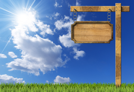 metallic  sun: Empty rectangular wooden sign with metallic brown frame hanging with metal chain on a wooden pole on blue sky with clouds sun rays and green grass Stock Photo