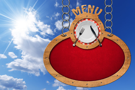 Oval sign with wooden frame white plate with silver cutlery and text menu. Hanging from a metal chain on blue sky with clouds and sun rays photo