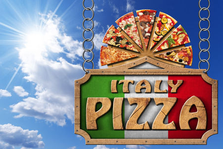 chain food: Wooden sign with frame and text Italy pizza slices of pizza on cutting board. Hanging on a metal chain on blue sky with clouds and sun rays