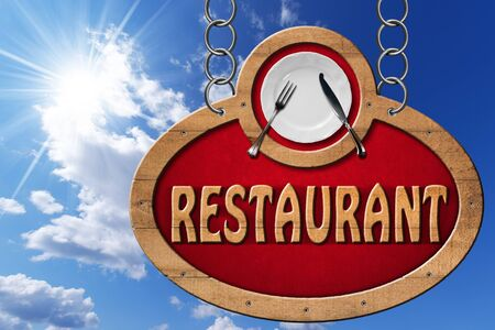 Wooden sign with frame white plate with silver cutlery and text restaurant. Hanging from a metal chain on blue sky with clouds and sun rays photo