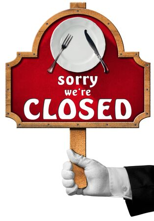 sorry: Hand of waiter with white glove holding a wooden pole with sign with empty white plate silver cutlery and text Sorry we are closed. Isolated on white Stock Photo