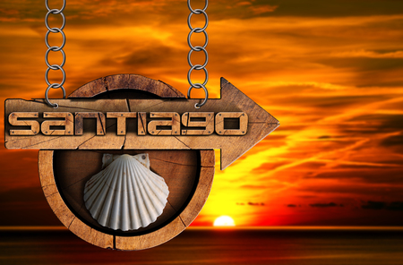 camino: Pilgrimage wooden sign of Santiago de Compostela Camino de Santiago with an arrow and seashell. Hanging from a metal chain at sunset over the sea with cloudy sky