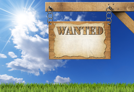 Wooden sign with planks and torn empty parchment with text Wanted. Hanging from a metal chain on a wooden pole on blue sky with clouds and sun rays photo