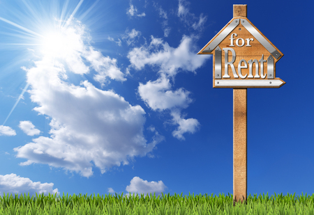 metallic  sun: Wooden and metallic sign in the shape of house with text for rent and wooden pole. For rent real estate sign on blue sky with clouds sun rays and green grass Stock Photo