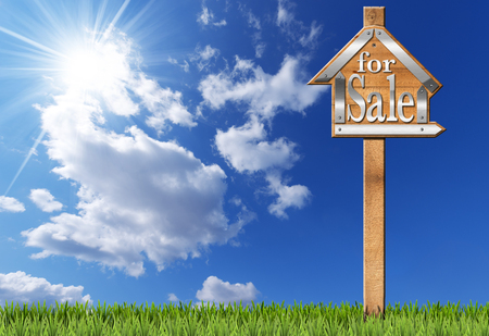 metallic  sun: Wooden and metallic sign in the shape of house with text for sale and wooden pole. For sale real estate sign on blue sky with clouds sun rays and green grass
