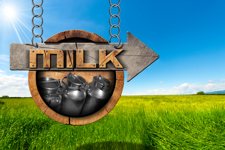 steel  milk: Wooden sign with directional arrow with text Milk and steel cans for the transport of milk. Hanging from a metal chain in a countryside landscape