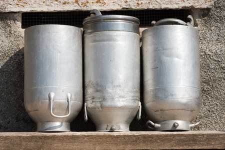 milk cans: Three old milk cans made of aluminum to dry on a wooden bench Stock Photo