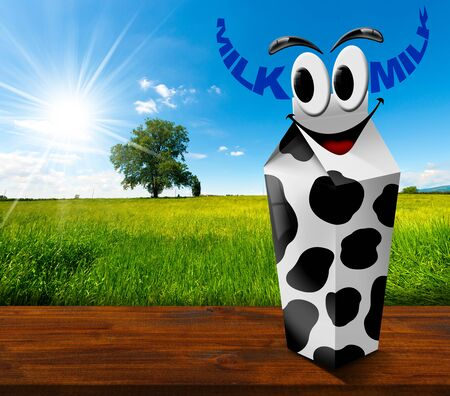 White carton milk with black spots with text Milk in the shape of horns. In a countryside landscape with green grass and a tree on blue sky with clouds and sun rays photo