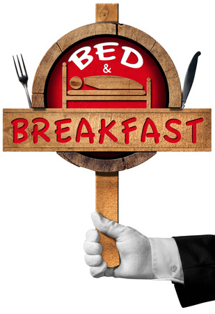 breakfast in bed: Hand of a concierge holding a wooden and red sign with text Bed and Breakfast and silver cutlery. Isolated on white background