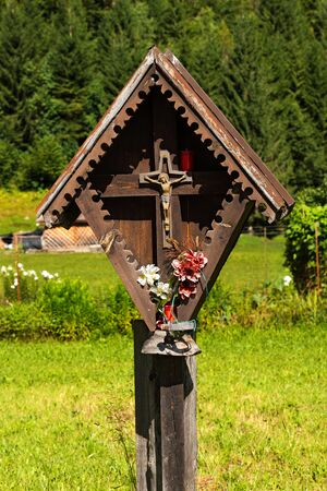 crucify: Typical wooden wayside shrine with jesus on cross in Italian alps. Trentino Alto Adige, Italy