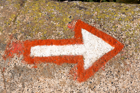marking up: Red and white arrow painted on a rock of mountain. Hiking trail sign symbol in Italy alps Stock Photo