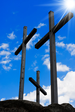 inri: Three wooden crosses on a blue sky with clouds and sun rays on a hill. Symbol of Jesus crucifixion Stock Photo