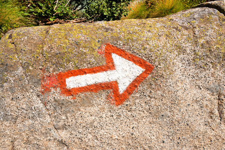 trail sign: Red and white arrow painted on a rock of mountain. Hiking trail sign symbol in Italy alps Stock Photo