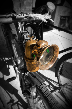 dynamo: Detail of an old Italian bicycle, in black and white and colors, with headlight and dynamo