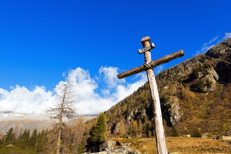 crucify: Old wooden cross trunks of trees tied with ropes with blue sky and clouds in the National Park of Adamello Brenta. Trentino Alto Adige, Italy