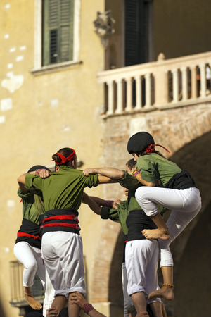 humanity: VERONA, ITALY - SEPTEMBER 19, 2015: Tocati, International festival of street games. Castells Performance of Xiquets dAlcover of Tarragona, Catalonia, Spain. The Castells Castle in Catalan is a human tower -  intangible cultural heritage of humanity