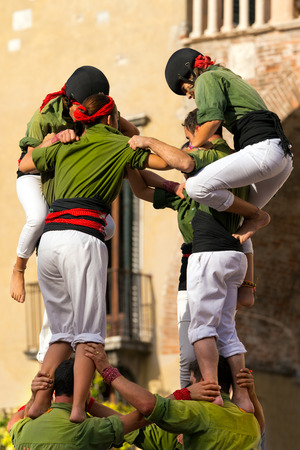 intangible: VERONA, ITALY - SEPTEMBER 19, 2015: Tocati, International festival of street games. Castells Performance of Xiquets dAlcover of Tarragona, Catalonia, Spain. The Castells Castle in Catalan is a human tower -  intangible cultural heritage of humanity