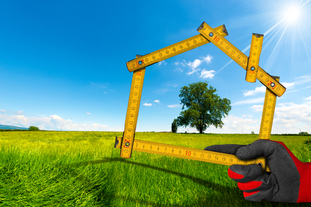 project: Hand with work glove holding a wooden meter ruler in the shape of house, in the countryside with green tree. Concept of ecological house project
