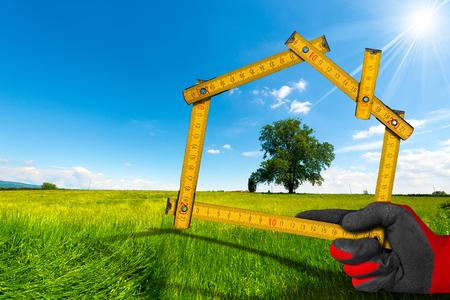 Main avec gant de travail tenue d'une règle de mètre en bois en forme de la maison, à la campagne avec arbre vert. Concept de projet de maison écologique
