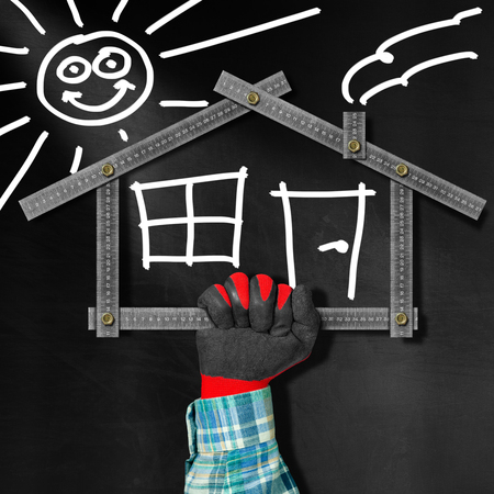 ruler: Hand holding a metal meter ruler in the shape of house with sun, door, window and smoke from the chimney. On a blackboard. Concept of house project
