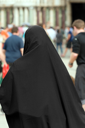 view from behind: Traditional Muslim woman with black veil view from behind Stock Photo
