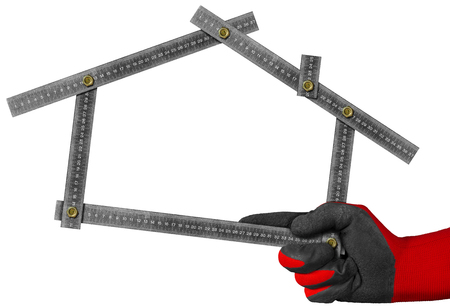 work glove: Hand with red and black work glove holding a metal meter ruler in the shape of house isolated on white background. Concept of house project Stock Photo