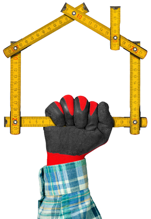work glove: Hand with red and black work glove holding a yellow wooden meter ruler in the shape of house isolated on white background. Concept of house project