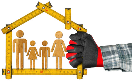 ruler: Hand with work glove holding a wooden meter ruler in the shape of house with symbol of a family. Isolated on white. Concept of house project
