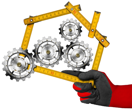 work glove: Hand with work glove holding a yellow wooden meter ruler in the shape of house with gears, symbol of house industry. Isolated on a white background Stock Photo