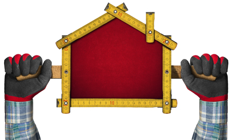 Hände mit Arbeitshandschuhen hält ein Holzlineal Meter in der Form des Hauses isoliert auf weißem Hintergrund. Konzept der Hausprojekt