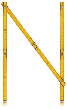 vintage: Oude houten gele meter in de vorm van de letter N. geïsoleerd op een witte achtergrond. Stockfoto