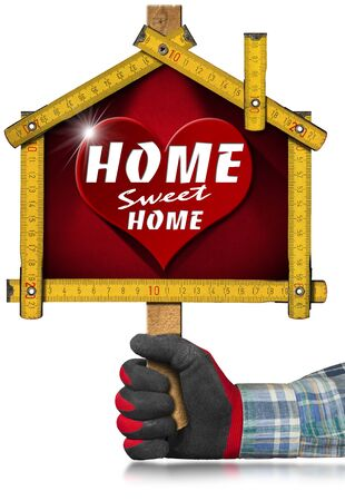 wooden work: Hands with work glove holding a yellow wooden meter ruler in the shape of house with text Home sweet home. Isolated on white background