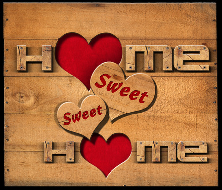 Wooden text Home sweet home with two hearts on a wooden wall isolated on a black background