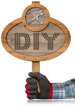 wooden work: Hand with work glove holding a oval wooden sign with text Diy Do it yourself and a symbol with hammer and wrench. Isolated on white background Stock Photo