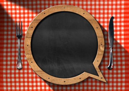 Empty blackboard in the shape of speech bubble on a table with red and white checkered tablecloth and silver cutlery. Template for a restaurant menu