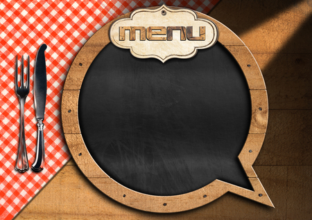 Restaurant menu with empty blackboard in the shape of speech bubble on a wooden background with silver cutlery and checkered tablecloth