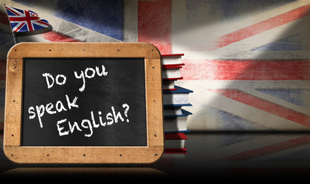 speak english: Blackboard with wooden frame and text Do you speak english A stack of books on a wall with Uk flag