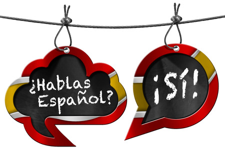 Two speech bubbles with Spanish flag and text Hablas Espanol Si! Hanging from a steel cable and isolated on white