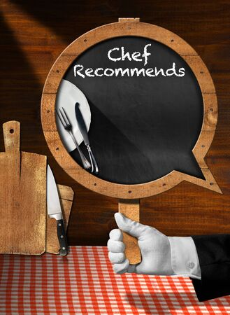 checker plate: Hand of chef with white glove holding a pole with empty blackboard in the shape of speech bubble with text Chef Recommends Stock Photo