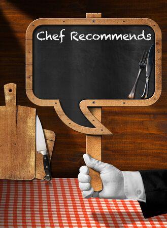red sign: Hand of chef with white glove holding a pole with empty blackboard in the shape of speech bubble with text Chef Recommends Stock Photo