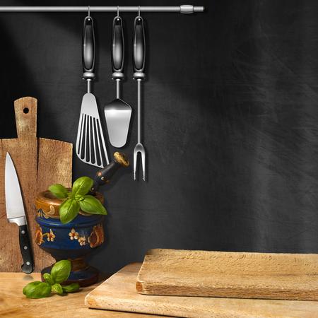 Pizarra vacía en la pared, mortero y mortero con hojas de albahaca, tablas de cortar y utensilios de cocina. Plantilla para recetas o menú de la comida Foto de archivo