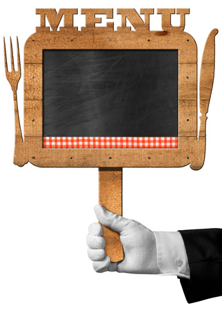 old frame: Hand of chef with white glove holding an old empty blackboard with wooden frame with text menu, wooden cutlery and checkered tablecloth Stock Photo