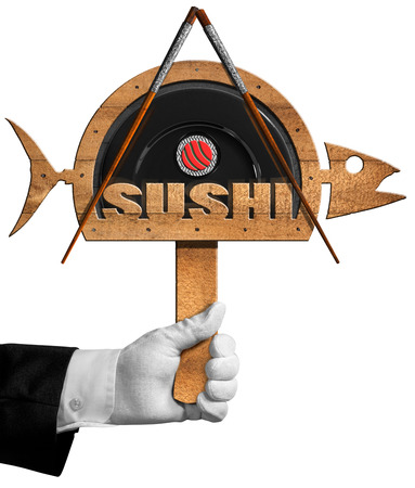 waiter: Chef holding a wooden symbol in the shape of fish with black plate, chopsticks, sushi roll and text Sushi. Isolated on white