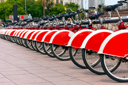 shared sharing: Long row of red and white bicycles public bikes near the harbor in Ronda Litoral, Barcelona - Spain Stock Photo