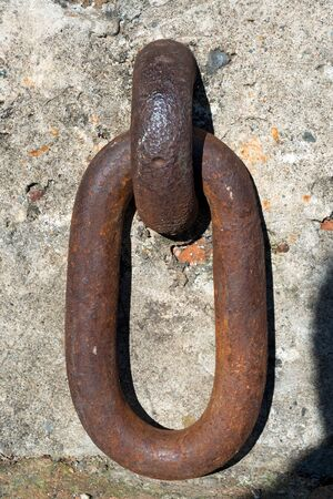 rusty chain: Close up of a large and rusty iron ring hanging a wall