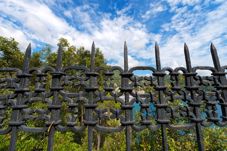iron gate: Old wrought iron fence painted with black color. Blue sky with clouds and green trees on background
