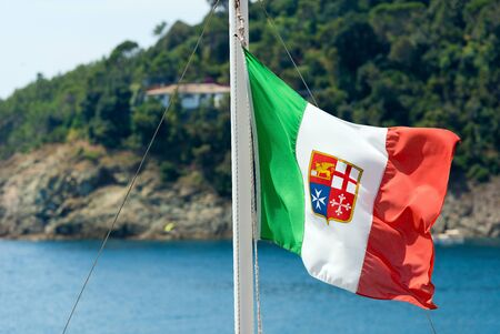 republics: Italian flag with emblem of the four Maritime Republics, Venice, Genoa, Pisa and Amalfi hanging on a ships mast. Blue sea on the background Stock Photo
