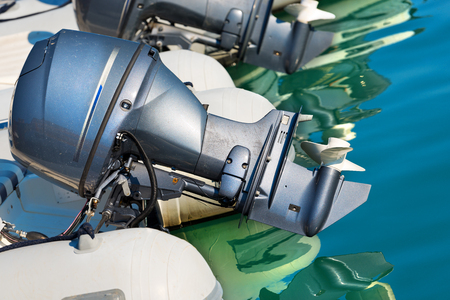 Detail of two outboard used engines, on an inflatable boat on the water with reflections