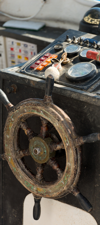 helm boat: Detalle de una vieja consola borrosa con rueda de timón de madera de un barco de pesca. Liguria, Italia