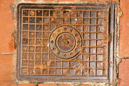 Metal brown rusty manhole cover on a pedestrian walkway